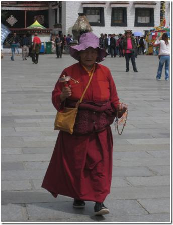 藏族朝圣者转着经轮走在拉萨大昭寺前,已找不到任何2008年广场骚乱的痕迹了。(照片:Jannuzi)
